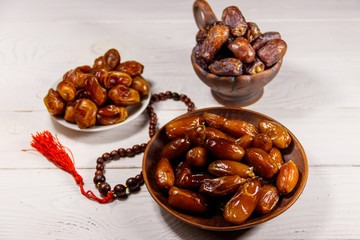 Dates fruit and rosary on white wooden table