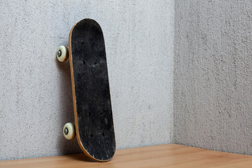 Skateboard standing on a wall.