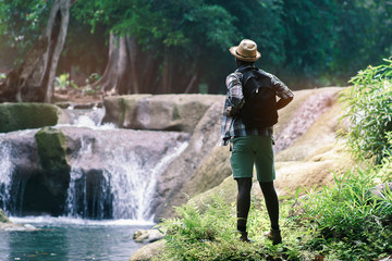 African Man Traveler with backpack standing and relaxing outdoor with waterfall