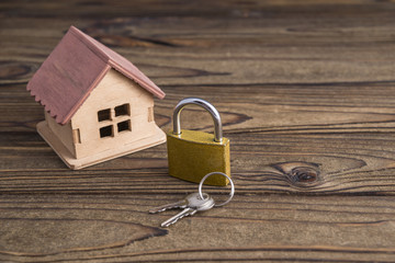 Concept of a small house and a golden lock with keys. on a natural wooden background. The idea: security, protection, alarm, law and order.