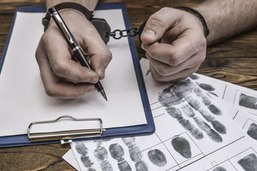 Men's hands with handcuffs fill the police record, confession. on top of the police investigative detective. Arrest, bail, criminal, prison. fingerprints, criminalist. the attacker. close-up