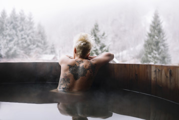 Tattooed blonde woman swimming in plunge tub