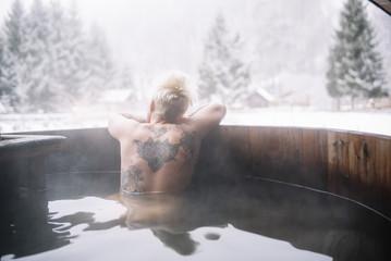Tattooed blonde woman swimming in plunge tub