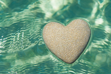 Heart made of sand floating in transparent ocean ripples water background, Saint Valentines day greeting cards, romantic love or proposal concept.