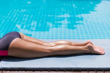 slim woman legs sunbathe near pool