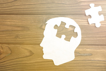 head of a man from a paper on a wooden background. puzzle piece. think. idea. business vision.