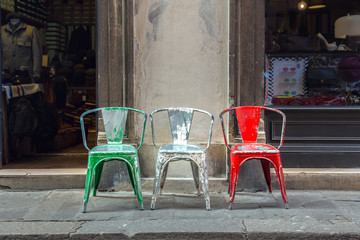 Red, white and green chairs in a row on a street outside. Italian flag concept