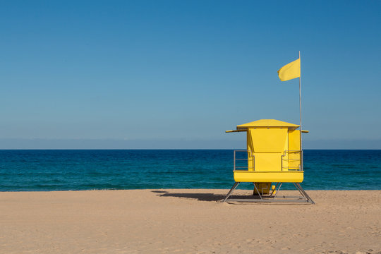 Yellow beach safety flag warning. Lifeguard tower. Lifeguards are on patrol