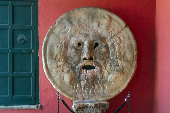 Carved stone human face Bocca della Verita or Mouth of Truth sculpture indoors in Rome