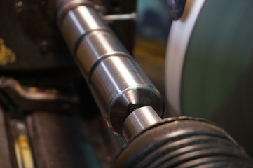 Shaft machining on a circular grinding machine in a production with a spark