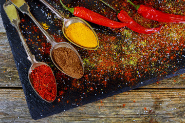Deurstickers Kruiden Overhead view depicting cooking with spices in a rustic kitchen with bowls of colourful ground spice and scattered powder on an old wooden