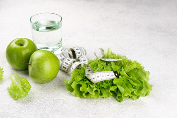 Healthy eating and diet background. Green apple, lettuce salad, glass of water, measuring tape. Dieting, slimming, weight loss concept. Top view. Copy space