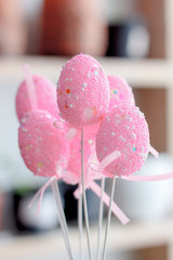 Pink easter eggs on a sticks over the bright background.