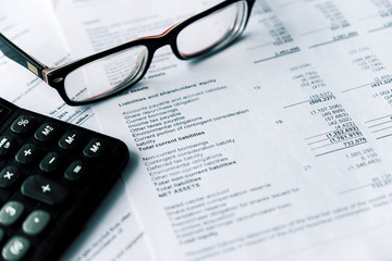 Financial statement and eyeglass, business concept, document is mock-up
