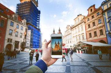 Photo camera of smartphone and old Prague centre with famous sightseeing. Old city square with people during the sunset