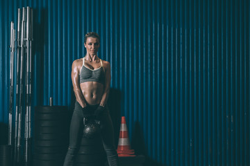 Fit woman training working out lifting kettlebell in Gym