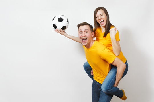 Inspired young couple, woman sit on man piggyback, fans with soccer ball cheering favorite football team expressive gesticulating hands isolated on white background. Family leisure, lifestyle concept.