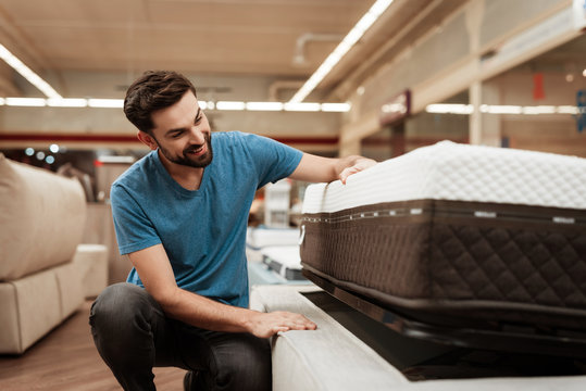 Young bearded man is testing mattress in furniture store. Orthopedic mattress for a healthy posture.
