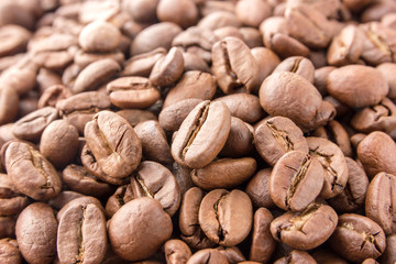 Coffee grains are scattered all over the surface. Roasted coffee beans close-up.