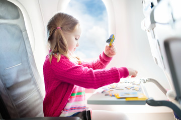 Child in airplane. Fly with family. Kids travel.