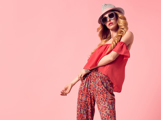 Wall Mural - Fashion Young Woman in Summer Stylish Outfit. Wavy Hair, Trendy pants, Luxury Sunglasses, fashion Hat. Fashionable Beautiful Blond Lady. Slim Playful Model Girl Posing in Studio