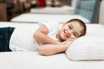 Smiling little girl lies on n orthopedic mattress in a furniture store.