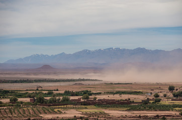Poster de jardin Maroc Sandstorm in valley near of High Atlas mountain range. With snow on the peaks at background. Morocco