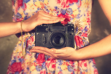 camera in the hands of a girl in a beautiful dress in a flower