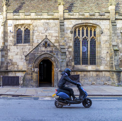 Man wearing helmet riding on a motor scooter driving past a church that has been converted into a bar and nightclub in York, England, United Kingdom showing past and present
