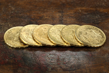 Belgian 20 Francs gold coins on rustic wooden background