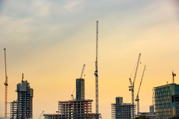 New skyscrapers under construction with tall cranes against yellow sky. Construction business and industry, urbanisation, urban sprawl real estate bubble concept, background with copy space.
