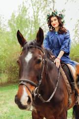 cute girl in a beautiful blue dress sitting on a horse. big flower wreath on head of nice woman