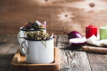 Sea kale salad with red onion in white rustic mug