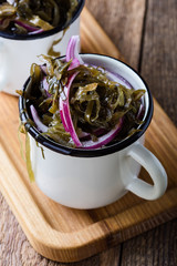 Sea kale salad with red onion in rural white mugs