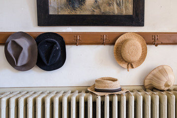 Wall hanger with various hats on it, radiator and old painting