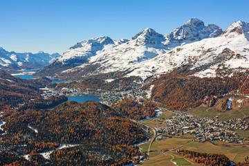 Blick über das Engadin in den Schweizer Alpen. Herbstlandschaft mit schneebedeckten Bergen, Wäldern, Seen und den Orten St. Moritz und Celerina in Graubünden, Schweiz