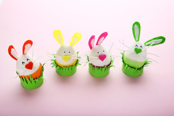 Eggs with funny rabbit faces on pink background