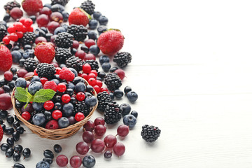 Ripe and sweet berries in basket on white wooden table