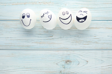 Eggs with funny faces on wooden table