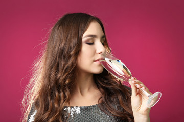 Young woman with glass of champagne on pink background