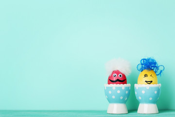 Eggs with funny faces on mint background