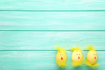 Yellow eggs with funny chicken faces on wooden table