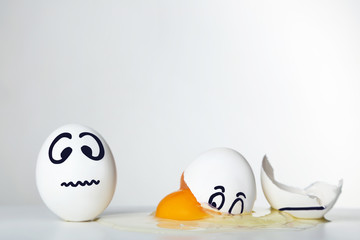 Eggs with funny faces on grey background