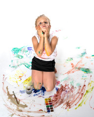 A little girl draws paints on her body