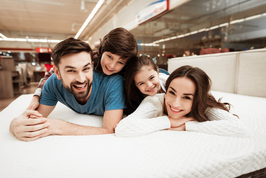 Little children lie on the backs of young happy parents in a mattress store.