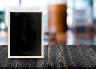 Empty wooden table with chalkboard in restaurant blur background, blackboard on wood - can be used for display your products.