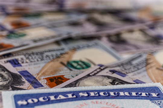 Social Security card and a bed of money representing the high cost of living on a fixed income I