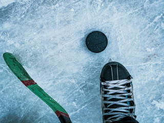 hockey puck stick and skates on ice texture top down view with copyspace