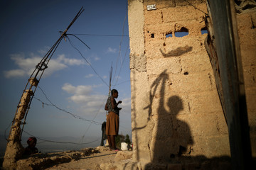 The shadow of a boy flying a kite casts on a wall in a slum of Port-au-Prince