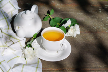 Hot green tea in a teapot and cup with a branch of jasmine flowers blossom  and white towel on rough rustic brown wooden background.  Nature healthy slow life concept. Copy space, top view.
